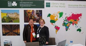 Helen Mandl and Caroline Saccucci in front of a poster of Librrary Map of the World